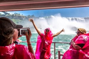 A group of tourists having fun using red raincoats inside a boat close to the falls in Niagara Falls, Canada