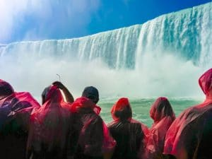 POV of Niagara Falls from a boat tour. Tourists dressed in raincoats stand on a tour boat as it approaches Niagara Falls